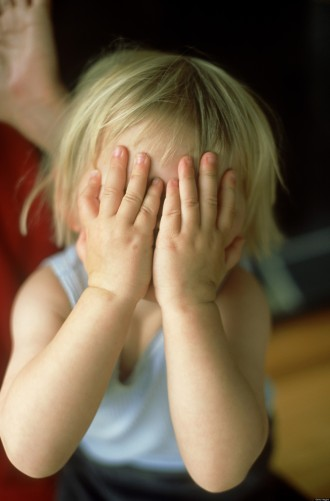 little girl (2-3 years) hiding behind hands